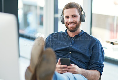 Buy stock photo Shot of a young businessman using a smartphone and headphones in a modern office
