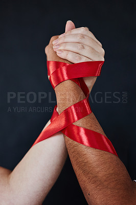 Buy stock photo Studio shot of two unrecognisable women bound together, holding their hands in solidarity against a dark background
