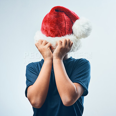 Buy stock photo Studio shot of a cute little boy covering his head with a Santa hat against a grey background