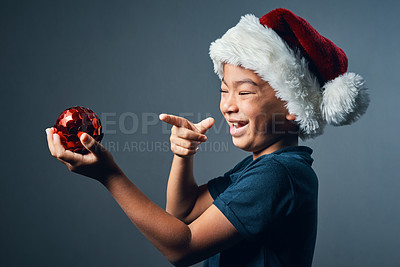 Buy stock photo Studio shot of a cute little boy playing with a Christmas decoration against a grey background