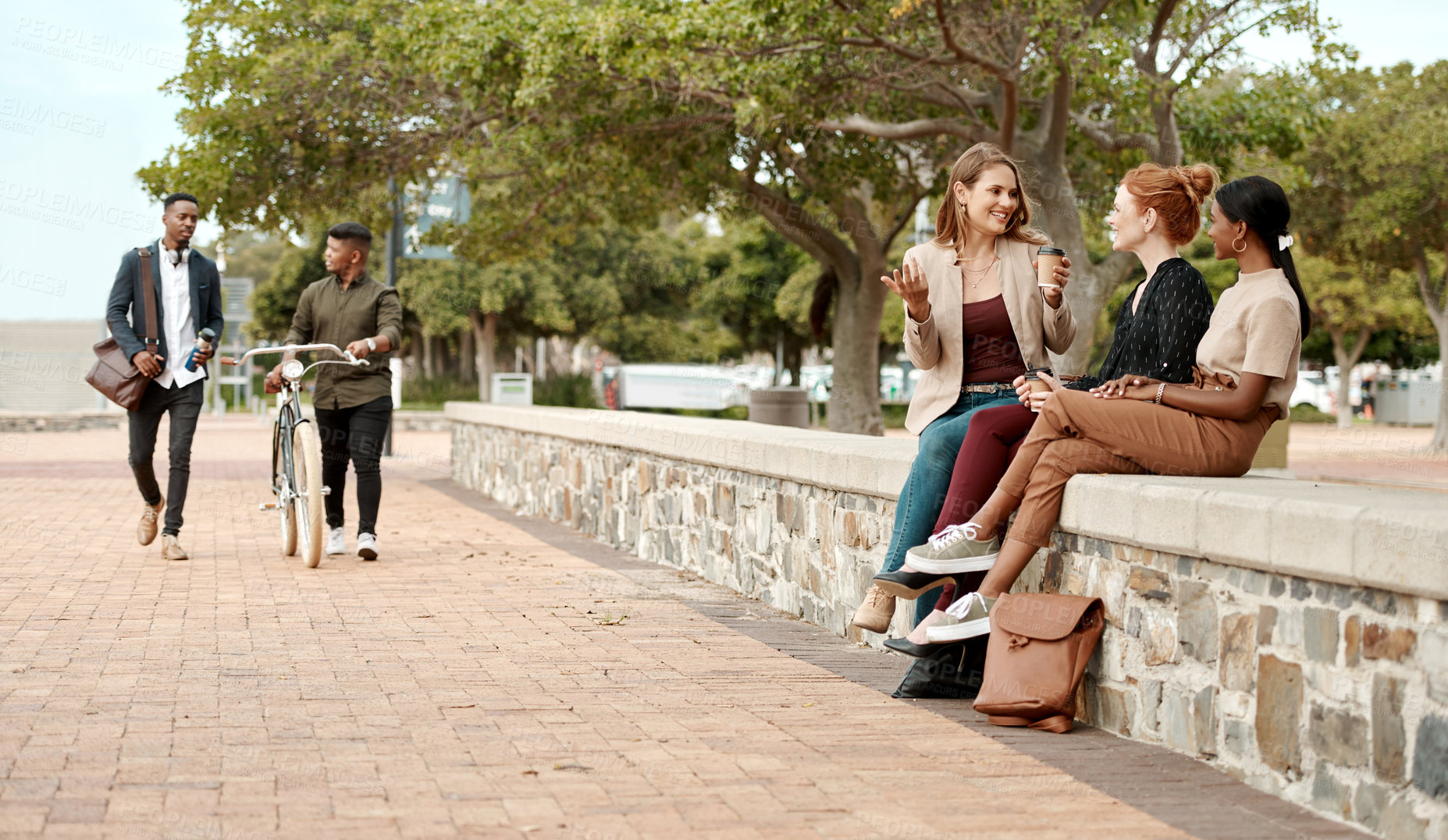 Buy stock photo Shot of a group of young businesswomen chatting during a coffee break in the city