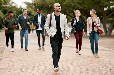Buy stock photo Shot of a confident mature businessman walking through the city with a young team behind him