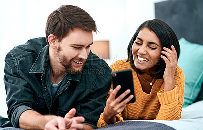 Buy stock photo Shot of a young couple using a smartphone together on their bed at home