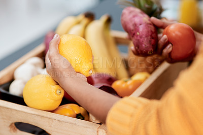 Buy stock photo Cropped shot of a woman unpacking her groceries in the kitchen at home