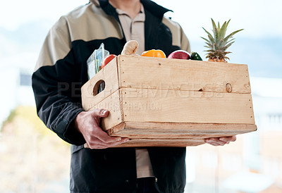 Buy stock photo Cropped shot of a man delivering fresh fruit and vegetables to a place of residence