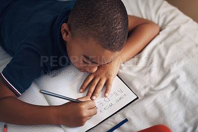 Buy stock photo Shot of a young boy using a pencil while writing at home