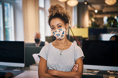 Buy stock photo Cropped portrait of an attractive young businesswoman standing with her arms crossed in the office while wearing a mask