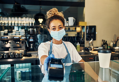 Buy stock photo Shot of a masked young woman serving coffee with a credit card machine in a cafe