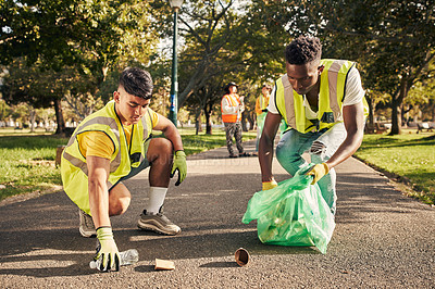 Buy stock photo Full length shot of two young male volunteers doing community service in the local park with their friends in the background