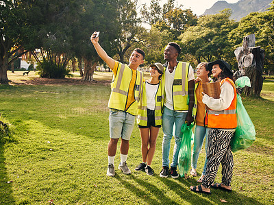 Buy stock photo Full length shot of a group of young volunteers taking selfies while doing community service in their local park