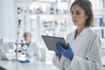 Buy stock photo Shot of a mature scientist using a digital tablet in a lab with her colleague in the background