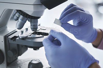 Buy stock photo Closeup shot of an unrecognisable scientist using a microscope in a lab