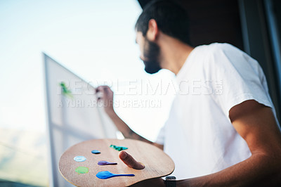 Buy stock photo Cropped shot of a man painting on a canvas while sitting on the balcony at home