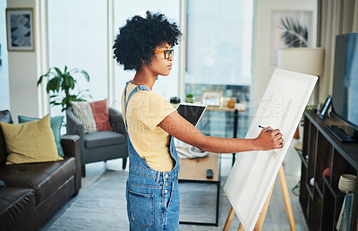 Buy stock photo Shot of a young artist holding a digital tablet while drawing  on a canvas at home