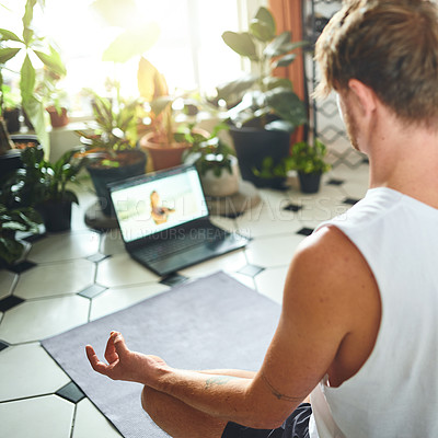 Buy stock photo Shot of a young man using a laptop while meditating in the lotus position at home