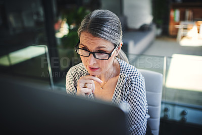 Buy stock photo Shot of a mature businesswoman using a computer in a modern office
