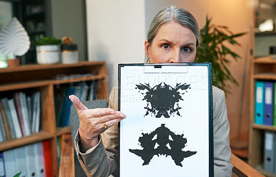 Buy stock photo Portrait of a mature psychologist holding up an inkblot test during a therapeutic session