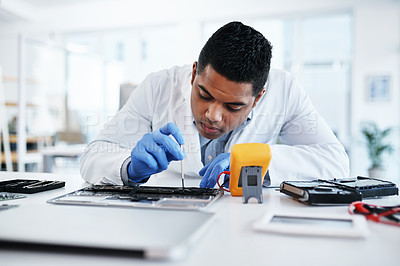 Buy stock photo Shot of a young man repairing computer hardware in a laboratory