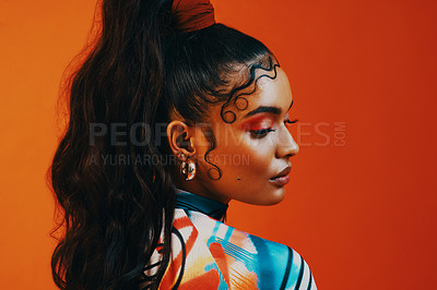 Buy stock photo Shot of a young woman posing against a orange background with a trendy hairstyle