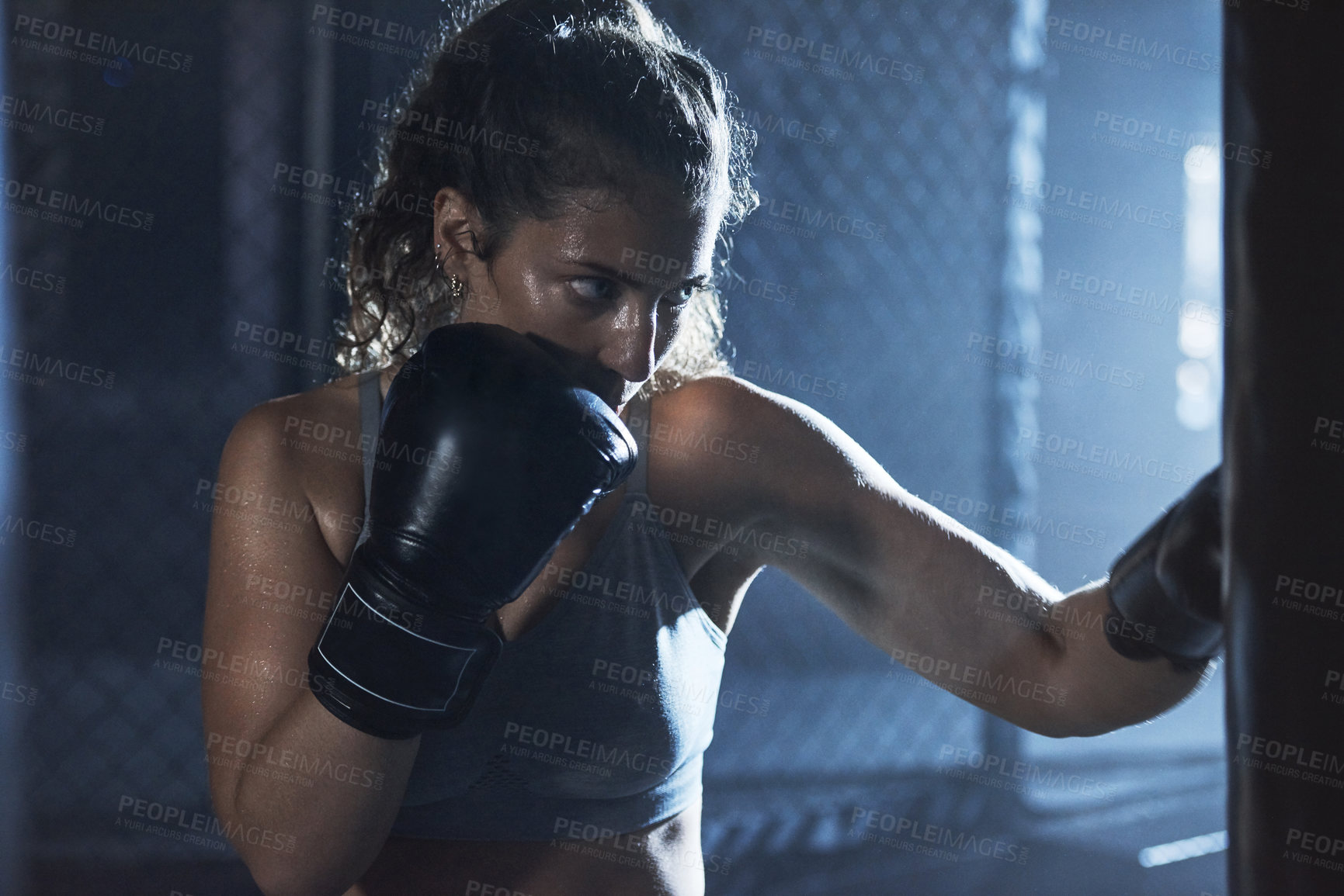 Buy stock photo Shot of a sporty young woman boxing in a gym