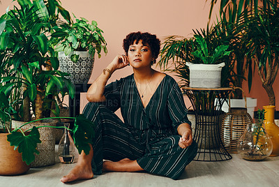 Buy stock photo Shot of a beautiful young woman sitting on the floor with multiple houseplants behind her