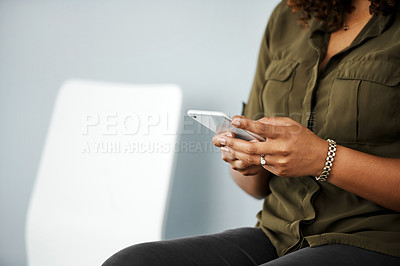 Buy stock photo Shot of a businesswoman using her smartphone while waiting in line