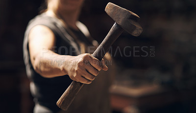 Buy stock photo Cropped shot of a woman holding a hammer while working at a foundry