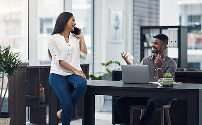 Buy stock photo Shot of a young businesswoman talking on a cellphone while her colleague is shrugging at her in an office