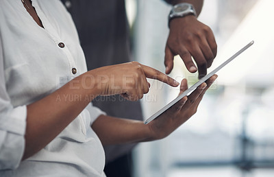 Buy stock photo Closeup shot of two unrecognisable businesspeople working on a digital tablet together in an office