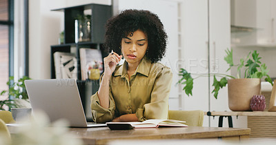 Buy stock photo Shot of a young woman going through notes while working on a laptop at home