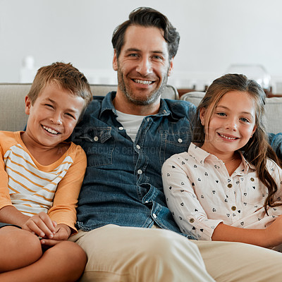 Buy stock photo Shot of a young boy and girl sitting at home with their father