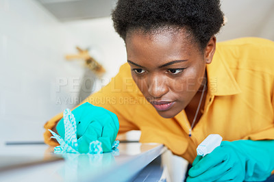 Buy stock photo Cropped shot of a young woman cleaning a kitchen counter at home