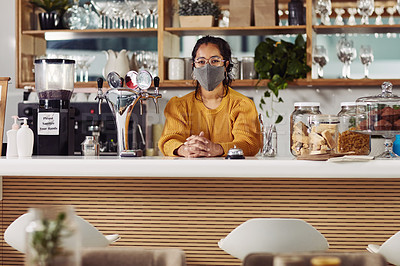 Buy stock photo Shot of a woman wearing a face mask while working in a cafe