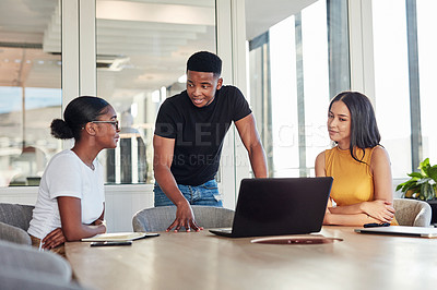 Buy stock photo Shot of a group of young businesspeople using a laptop during a meeting in a modern office