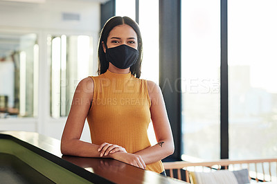 Buy stock photo Portrait of a confident masked young businesswoman standing at the front desk of a modern office