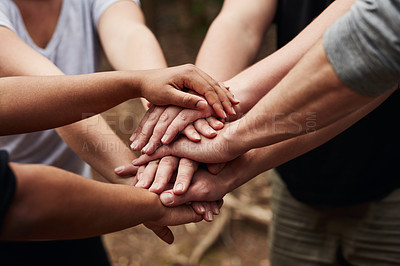 Buy stock photo Cropped shot of a group of unrecognisable people joining hands in solidarity out in nature