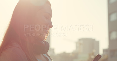 Buy stock photo Cropped shot of a woman using her cellphone while standing outside