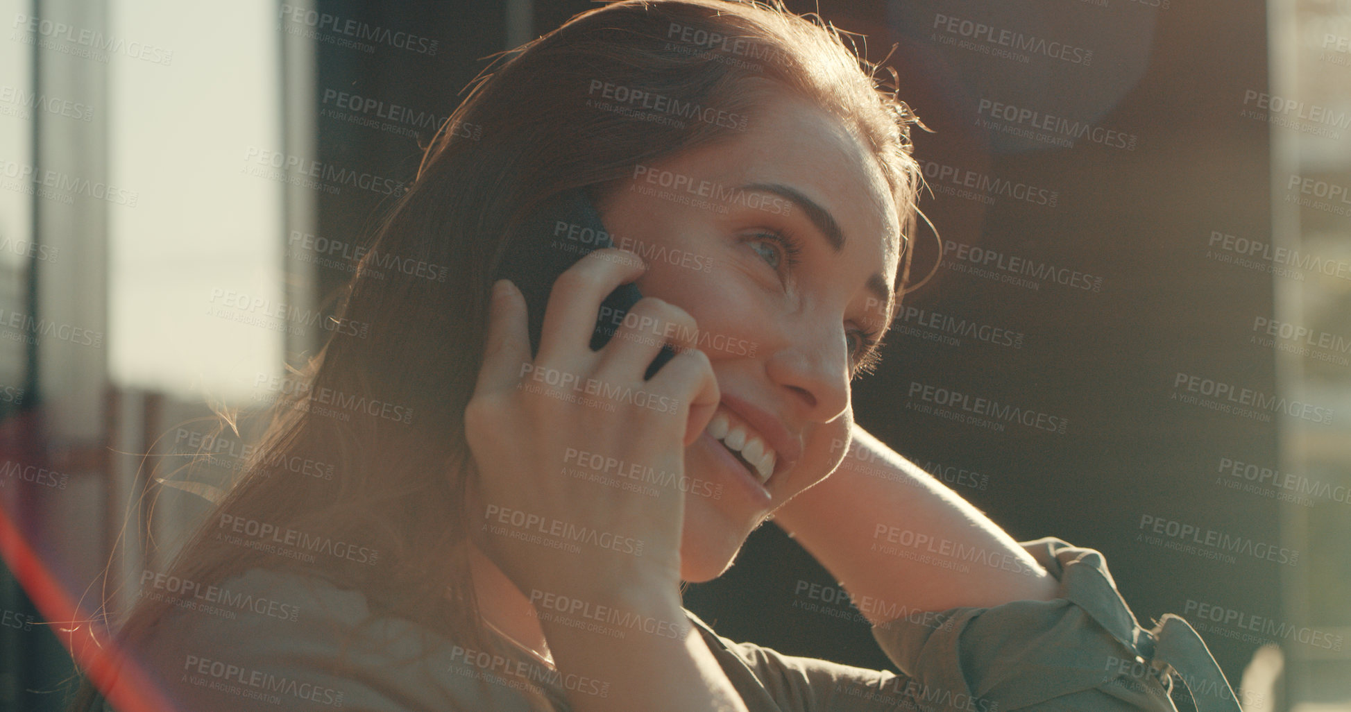 Buy stock photo Shot of a beautiful young woman talking on her cellphone while standing outside