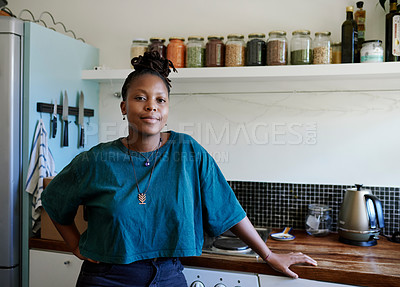 Buy stock photo Cropped shot of a young woman standing in the kitchen at home