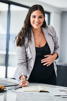 Buy stock photo Portrait of a pregnant young woman writing notes while working from home