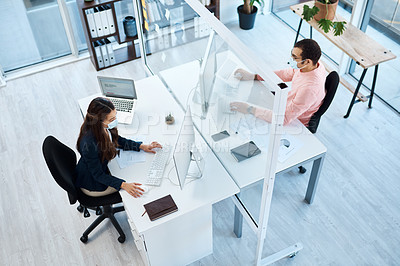 Buy stock photo High angle shot of two businesspeople wearing face masks while working in an office