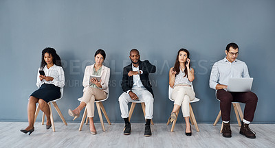 Buy stock photo Shot of a group of businesspeople using digital devices while sitting in line against a grey background