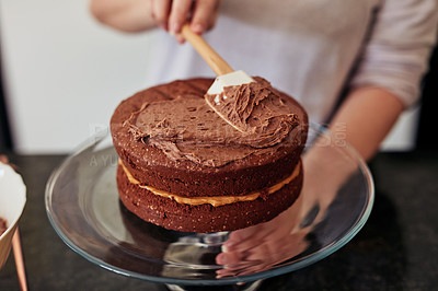 Buy stock photo Shot of an unrecognisable woman spreading buttercream on a freshly baked chocolate cake at home