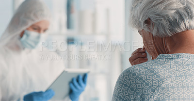 Buy stock photo Shot of a doctor using a digital tablet while caring for her senior patient