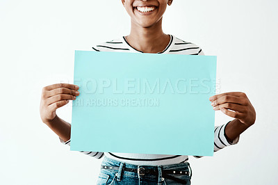 Buy stock photo Cropped studio shot of a woman holding a blue poster against a white background