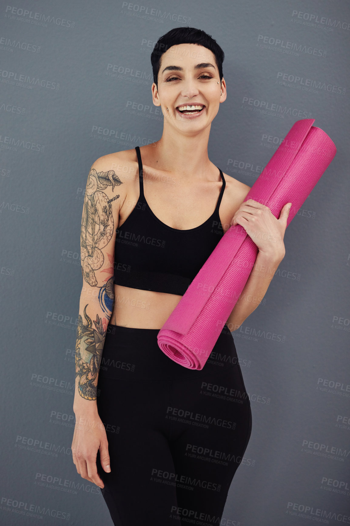 Buy stock photo Portrait of a confident young woman holding an exercise mat against a grey studio background