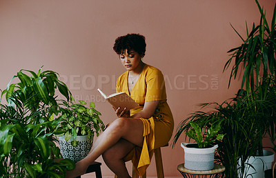 Buy stock photo Shot of a young woman reading a book while sitting with plants around her against a brown background