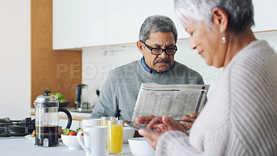 Buy stock photo Shot of a senior couple reading the paper and using a smartphone during a relaxing breakfast at home