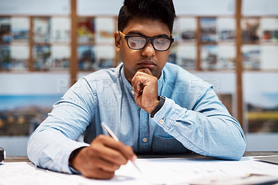 Buy stock photo Shot of a young architect designing a building plan in a modern office