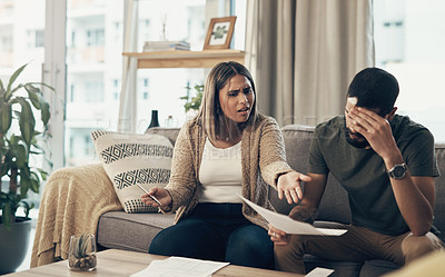 Buy stock photo Shot of a young couple having an argument while going over paperwork at home